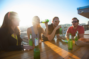 Four adult friends drinking beer at rooftop bar table with Los Angeles skyline, USAの写真素材 [FYI03529115]