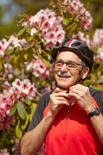 Senior man putting on cycle helmetの写真素材 [FYI03529178]