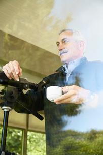 Senior man at home, drinking coffee, using telescope through windowの写真素材 [FYI03529189]