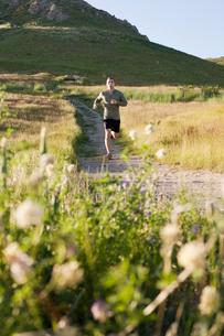 Young male runner running down hillside trackの写真素材 [FYI03529210]