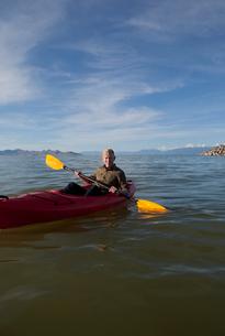 Young man in kayak holding paddles, looking at camera, Great Salt Lake, Utah, USAの写真素材 [FYI03529344]