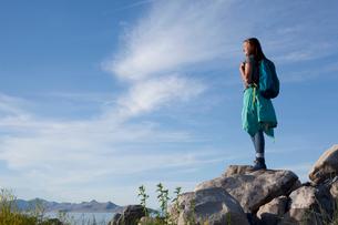 Rear view of young woman wearing backpack standing on rocks looking away, Great Salt Lake, Utah, USAの写真素材 [FYI03529352]