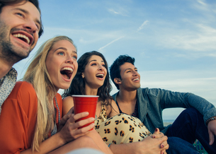 Group of friends sitting together outdoors, laughingの写真素材 [FYI03529453]