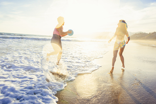 Young couple fooling around on beach, on sea, sunsetの写真素材 [FYI03529481]