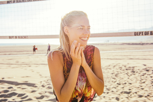 Young woman standing on beach by volleyball net, laughingの写真素材 [FYI03529495]