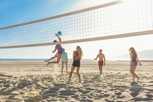 Group of friends playing volleyball on beachの写真素材 [FYI03529498]