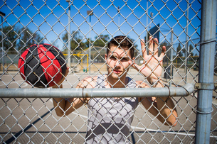 Portrait of young male basketball player behind basketball court fenceの写真素材 [FYI03529623]