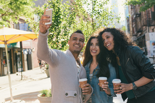 Three mid adult friends with takeaway coffees posing for smartphone selfie on city streetの写真素材 [FYI03529673]