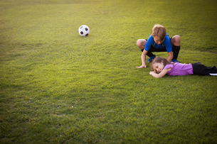 Boy tending injured younger sister on football practice pitchの写真素材 [FYI03529760]