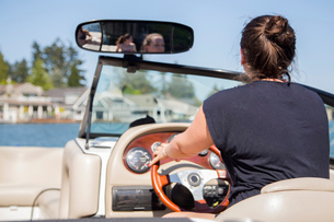 Rear view of young woman driving motor boat, Lake Oswego, Oregon, USAの写真素材 [FYI03529776]