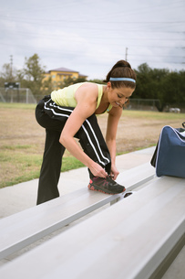 Soccer player tying shoe lace on benchの写真素材 [FYI03529816]