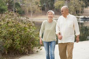 Senior couple walking along pathway, holding hands, laughingの写真素材 [FYI03530011]