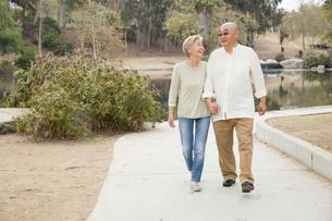 Senior couple walking along pathway, holding handsの写真素材 [FYI03530013]