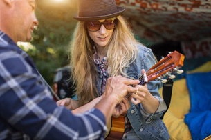 Mature man showing girlfriend how to play ukulele whilst camping in pick up bootの写真素材 [FYI03530160]