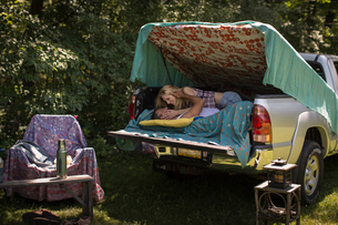 Young woman kissing boyfriend in pick up boot whilst campingの写真素材 [FYI03530166]