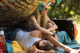 Young woman wearing headphones with boyfriend in pick up boot whilst campingの写真素材 [FYI03530169]