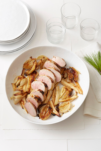 Still life of Pine-Roasted Pork Tenderloin with Parsnips and Onionsの写真素材 [FYI03530203]