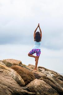 Rear view of mature woman practicing yoga tree pose on coastal rocks, Cape Cod, USAの写真素材 [FYI03530288]