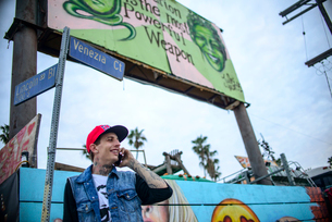 Graffiti artist using smartphone under street signs, Venice Beach, California, USAの写真素材 [FYI03530417]