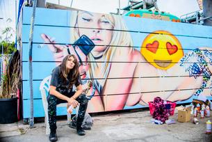 Graffiti artist sitting by painted wall, Venice Beach, California, USAの写真素材 [FYI03530419]