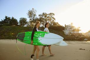 Couple walking towards sea, carrying surfboardsの写真素材 [FYI03530483]