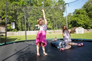 Three girls playing on trampoline in gardenの写真素材 [FYI03530494]