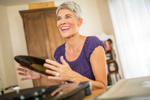 Happy mature woman playing vinyl recordsの写真素材 [FYI03530528]