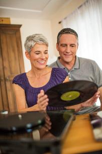 Romantic mature couple playing vinyl recordsの写真素材 [FYI03530529]