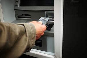 Mid adult man using cash machine, focus on handsの写真素材 [FYI03530572]