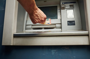 Mid adult man using cash machine, focus on handsの写真素材 [FYI03530573]