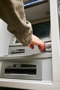 Mid adult man using cash machine, focus on handsの写真素材 [FYI03530574]