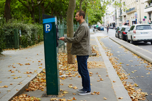 Mid adult man using parking meter in streetの写真素材 [FYI03530578]