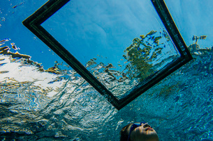 Teenage girl underwater, looking through frame on water surfaceの写真素材 [FYI03530650]
