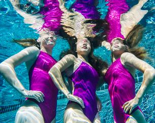 Three female swimmers, underwater, hands on hipsの写真素材 [FYI03530654]
