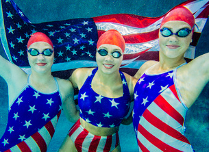 Three female swimmers, underwater, wearing stars and stripes costumes, holding american flagの写真素材 [FYI03530655]
