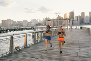 Two friends exercising together, running outdoors by riverの写真素材 [FYI03530719]