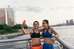 Two friends taking selfie photo after exercising together in running clothes next to riverの写真素材 [FYI03530735]