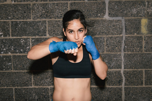 A young brunette woman exercising and boxing punching towards the cameraの写真素材 [FYI03530741]