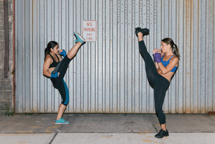 Two female friends exercising and kick boxing towards each otherの写真素材 [FYI03530744]