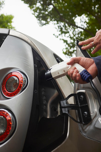 Man charging electric carの写真素材 [FYI03530789]