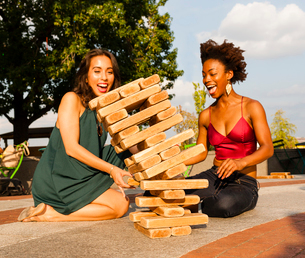 Young women playing with building blocks on floorの写真素材 [FYI03530838]