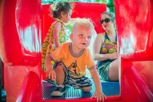 Mother and children playing on red playground slideの写真素材 [FYI03530963]