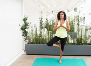 Mature woman doing yoga tree poseの写真素材 [FYI03531039]