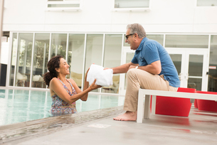 Senior man handing towel to wife from poolsideの写真素材 [FYI03531053]