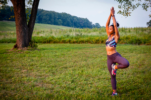 Young woman practicing yoga tree pose in rural parkの写真素材 [FYI03531071]
