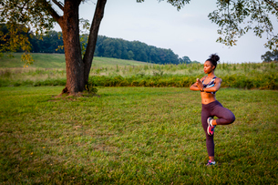 Young woman doing yoga tree pose in rural parkの写真素材 [FYI03531072]