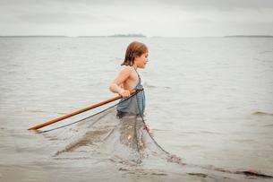 Girl learning how to use traditional fishing net, Sanibel Island, Pine Island Sound, Florida, USAの写真素材 [FYI03531097]