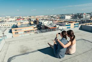 Businesswomen taking selfie with smartphone on roof terrace, Los Angeles, California, USAの写真素材 [FYI03531135]