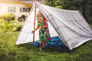 Portrait of girl peering from homemade garden tentの写真素材 [FYI03531198]