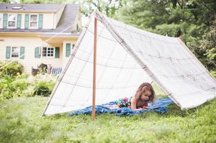 Girl lying in homemade garden tent using digital tabletの写真素材 [FYI03531205]